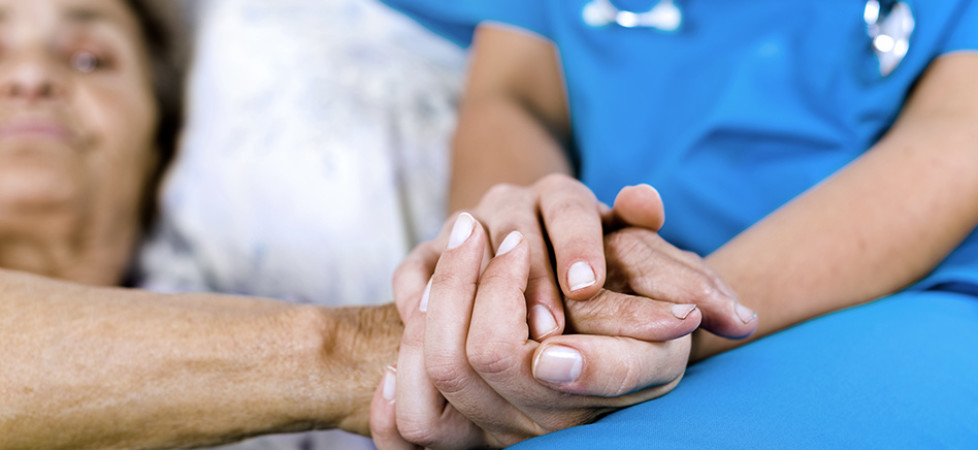 nurse holding elderly persons hand